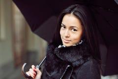 Sinnlig ung flickastående med paraplyet i ett regnigt väder Arkivbild
