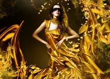 Sinnlig vuxen kvinna i guld- tyg Arkivfoto