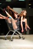 Sinnliga flickor med shoppingspårvagnen Royaltyfri Foto