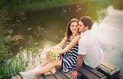 Sinnliga romantiska par som är förälskade på pir på sjön i solig dag Arkivfoto