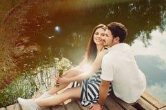Sinnliga romantiska par som är förälskade på pir på sjön i sommar da Arkivbild