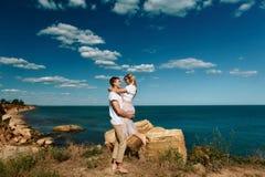 Sinnliga unga par i förälskat hopp för exponeringsglas på vaggar i havet nära stranden med stora klippor Man och kvinna som ser p royaltyfria foton