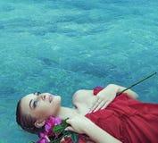 Sinnligt blont ligga i ett klart vatten arkivfoto