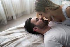 Sinnligt romantiskt förspel vid par i säng arkivfoto