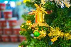 Sino amarelo no ramo da árvore de Natal no fundo Fotos de Stock Royalty Free