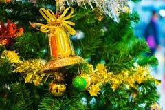 Sino amarelo no ramo da árvore de Natal no fundo Fotografia de Stock Royalty Free