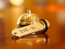 Sino e chave do hotel que encontram-se na mesa Fotografia de Stock Royalty Free