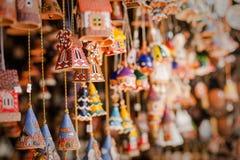 Sinos da lembrança e casas cerâmicos do brinquedo no mercado, local Fotos de Stock