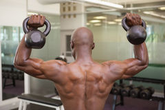 Sinos de levantamento da chaleira do homem muscular no gym Fotografia de Stock