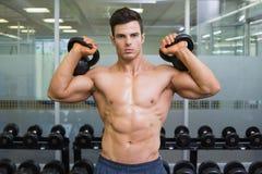 Sinos de levantamento da chaleira do homem muscular no gym Imagem de Stock