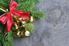 Sinos de Natal com ramo de árvore vermelho da fita e do abeto no fundo de madeira velho Decoração do Natal Imagens de Stock