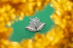 Sinos de Natal de prata decorativos cercados com ouropel dourado do bokeh no fundo verde imagem de stock royalty free