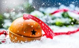 Sinos de tinir das bolas do Natal Fita vermelha com Natal feliz do texto Fundo abstrato nevado e decoração Foto de Stock