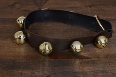 Sinos de trenó do ouro na madeira Imagem de Stock Royalty Free