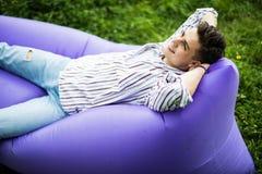 Sinta livre Homem novo considerável que encontra-se no lamzac inflável do sofá ao descansar na grama no parque foto de stock