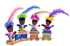 Sinterklaas. Four colorful black dolls on a toy train isolated Royalty Free Stock Images
