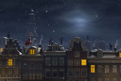 Sinterklaas and the Pieten on the rooftops at night Stock Photos