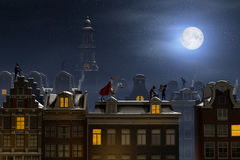 Sinterklaas and the Pieten on the rooftops at night Royalty Free Stock Photography