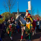 Sinterklaas rider hans vita häst tillsammans med hans assistenter arkivbilder