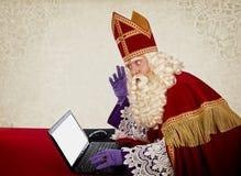 Sinterklaas or Saint Nicholas with laptop stock photo