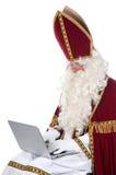 Sinterklaas using a laptop Royalty Free Stock Image