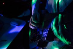 Sintetizador digital da guitarra preta na luz com mãos fotografia de stock