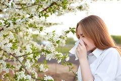 Sintomo di allergia del polline Il colpo all'aperto obliquo di giovane femmina europea starnutisce in fazzoletto o soffia nella s Fotografia Stock Libera da Diritti