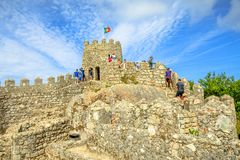 Sintra Mouros Castle. Sintra, Portugal - August 7, 2017: old wall and defensive tower of Castle of the Moors and Sintra valley, Lisbon District. People walk over Royalty Free Stock Photo