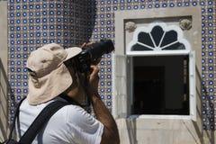 Sintra, Portugalia, Sierpień 25, 2018: mężczyzna w nakrętce fotografuje mozaikę Patrzeje viewfinder i trzyma jego palec na zdjęcie royalty free