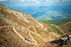 Sinuous path. Two hikers, male and female, climbing on a serpentine path in Rodnei Mountains, Romania. A town can be seen in the valley from the distance Royalty Free Stock Images