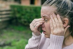 Sinus ache causing very paintful headache. Unhealthy woman in p. Closeup of young European female looking stressed, with closed eyes to overcome depression and Stock Photos