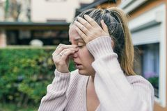 Sinus ache causing very paintful headache. Unhealthy woman in pa. In. Sharp strong sore. Sinus pain, sinus pressure, sinusitis. Sad woman holding her nose and Royalty Free Stock Image