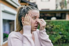 Sinus ache causing very paintful headache. Unhealthy woman in pa. In. Sharp strong sore. Sinus pain, sinus pressure, sinusitis. Sad woman holding her nose and Stock Photo