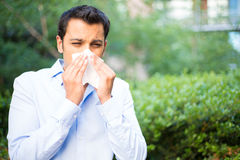 Sinus problems. Closeup portrait of young man in blue shirt with allergy or cold, blowing his nose with a tissue, looking miserable unwell very sick,  outside Stock Image