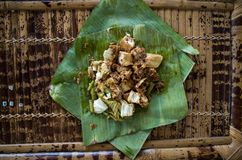 Siomay - Indonesian dish with steamed fish dumpling and vegetables served in peanut sauce in banana leaf - centered.  stock photos