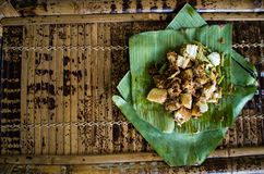 Siomay - Indonesian dish with steamed fish dumpling and vegetables served in peanut sauce in banana leaf - copy space left.  stock photo