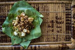 Siomay - Indonesian dish with steamed fish dumpling and vegetables served in peanut sauce in banana leaf - copy space right.  royalty free stock image