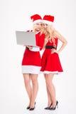 Siostra bliźniacy w Santa Claus ubierają i kapelusze z laptopem Fotografia Royalty Free