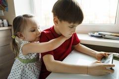 Siostra i brat siedzimy w kuchni i bawić się z telefonem zdjęcie royalty free