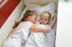 Siostry śpią na łóżku polowym w pociągu Zdjęcie Stock