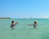 Siostry bawić się piłkę w zielonym pięknym oceanie Zdjęcia Royalty Free
