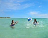 Siostry bawić się piłkę w zielonym pięknym oceanie Fotografia Royalty Free