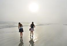 Siostry cieszy się czas wpólnie na pięknej mgłowej plaży Fotografia Royalty Free
