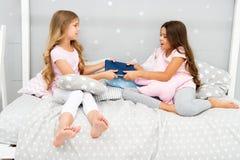 Siostry rywalizaci pojęcie Siostr powiązań zagadnienia Części książka z przyjacielem Dzieci w sypialni chcą czytającą wieczór cza fotografia stock