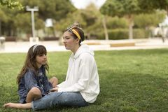Siostry siedzi na trawie z poważnymi twarzami obraz royalty free