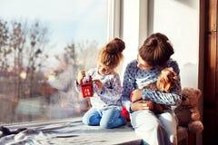 Siostry siedzi na windowsill z psem Pojęcie C zdjęcia stock
