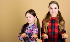 Siostry trzymają piec słodka bułeczka jest mógł karmowy domowej roboty kulebiak Diety kaloria i Yummy muffins Dziewczyna dzieciak fotografia royalty free