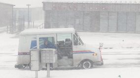 SIOUX CITY, IA - 17 JAN 2020: US Post Office postal carrier works to deliver mail in snow storm blizzard, going from his truck to