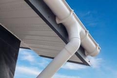 SIP设有暗门的妓院建筑 新的白色雨天沟 与塑料房屋板壁下端背面和房檐的排水系统反对蓝天 免版税库存图片