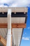 SIP设有暗门的妓院建筑 新的白色雨天沟 与塑料房屋板壁下端背面和房檐的排水系统反对蓝天 免版税图库摄影